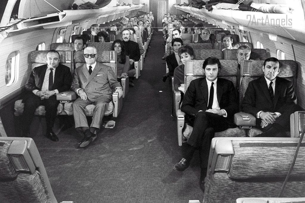 """Tournage du film """"Le CLAN DES SICILIENS"""" dans les studios de SAINT-MAURICE : toute l'Èquipe du film posant assis dans les fauteuils du Boeing reconstituÈ, avec avec de gauche à droite : Henri Verneuil, Jean Gabin, Alain Delon, Lino Ventura, et, Karen BLANGUERNON, IRINA DEMICK et Edward MEEKS (acteurs, producteur, directeur photo, assistants, rÈgisseur et cameraman parmi les autres passagers). - © Claude Azoulay"""