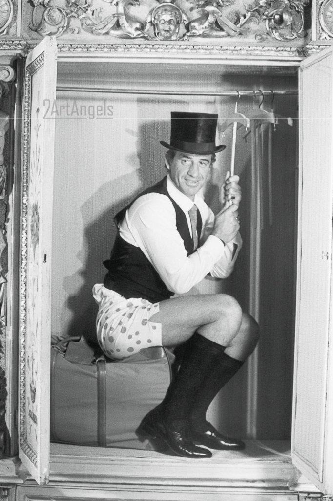 """Jean-Paul BELMONDO assis en calecon et chapeau haut-de-forme dans une penderie, lors du tournage du film """"Le guignolo"""" de Georges Lautner. - Venise, 1980 - © Claude Azoulay"""